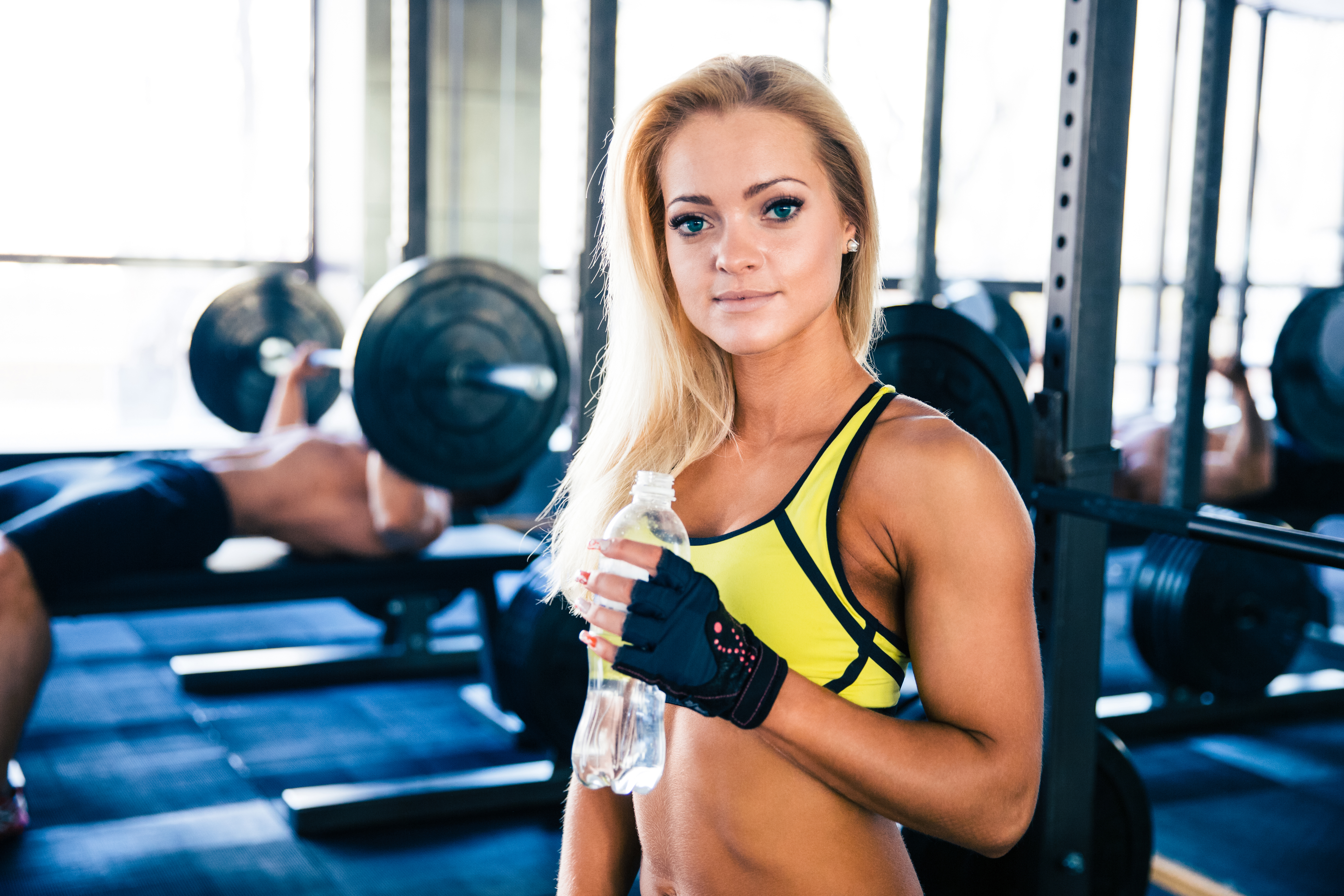 beautiful fitness woman holding bottle of water in gym HFgXySABo - Beautiful woman holding bottle of water in gym