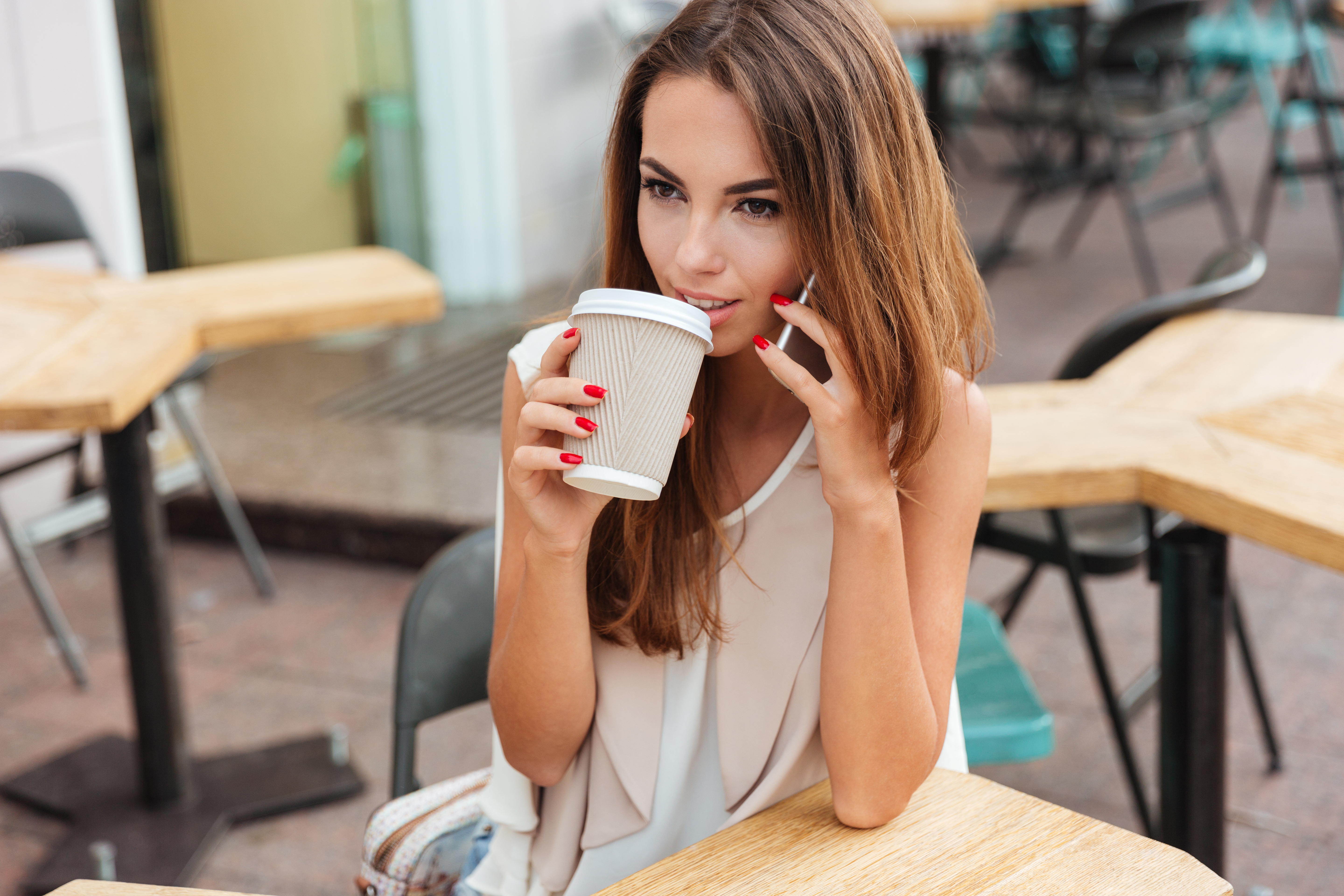 graphicstock smiling beautiful young woman drinking coffee and talking on cell phone while sitting in cafe SO7ZLLiHnx - Smiling beautiful woman drinking coffee and talking on cell phone